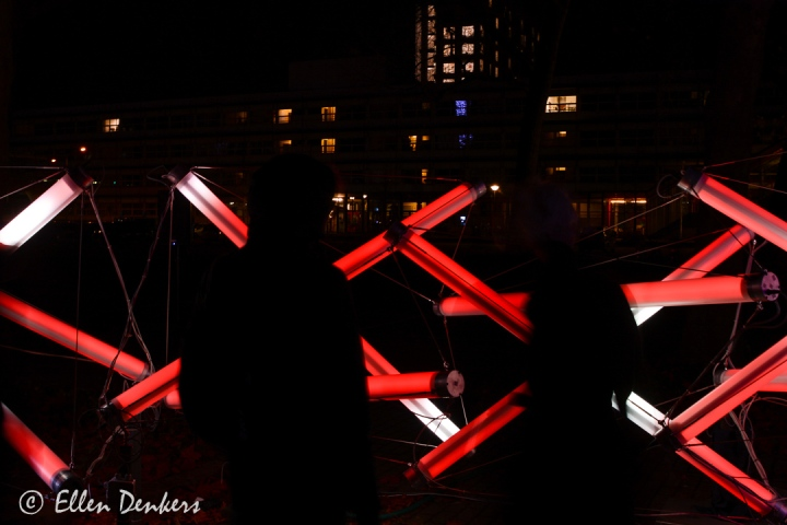 Glow - Lumenus - LumenUs is een door TU/e studenten ontwikkelde constructie die volledig is gebaseerd op een trek- en drukverhouding. De ingewikkelde constructie bestaat uit staven en staalkabels die elkaar in balans houden. In het kunstwerk worden de staven van binnenuit verlicht. Deze verlichting reageert op de impulsen van het GLOW publiek. Door deze interactie met het publiek nemen verschillende kleuren, door middel van sensoren, het object langzaam over.